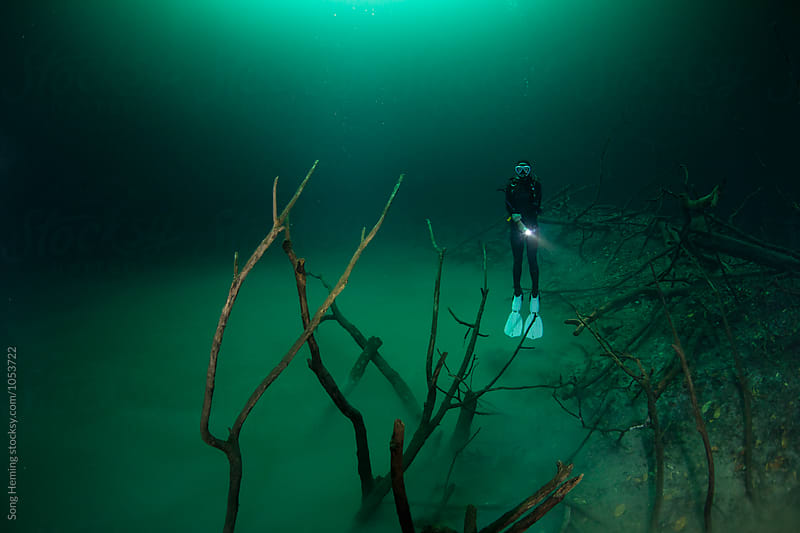 A scuba diver floating in Mexico's  Cenote Angelita by Song Heming for Stocksy United