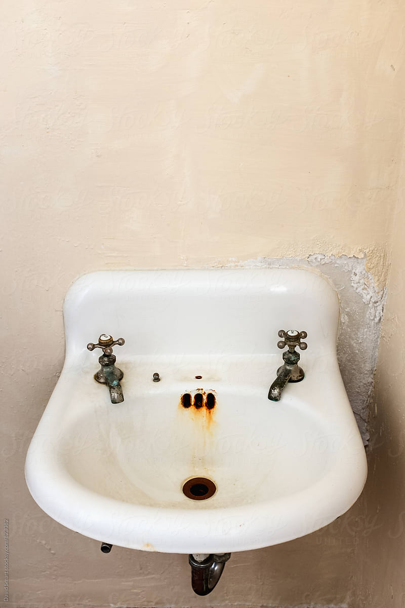 Old dirty porcelain bathroom sink on crumbling plaster wall. by David Smart for Stocksy United