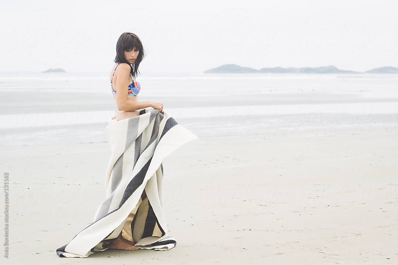 A woman in a bikini swaying on a beach playing with a blanket by Ania Boniecka for Stocksy United