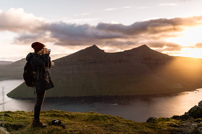 Woman Taking a Photo at a Mountain Overlook at Sunset by Daniel Inskeep for Stocksy United