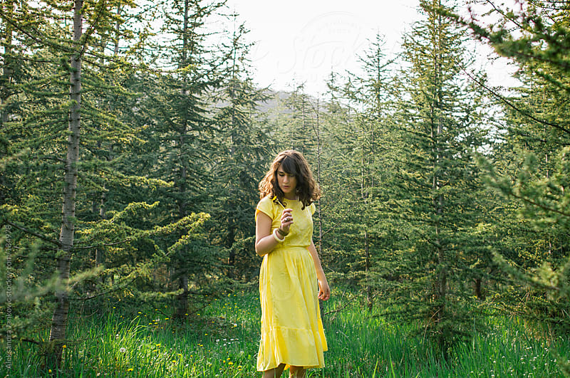 Girl in the yellow dress picks flowers in the woods by Aleksandra Jankovic for Stocksy United