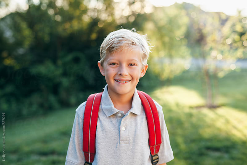 smiling student with backpack in the morning before school by Kelly Knox for Stocksy United