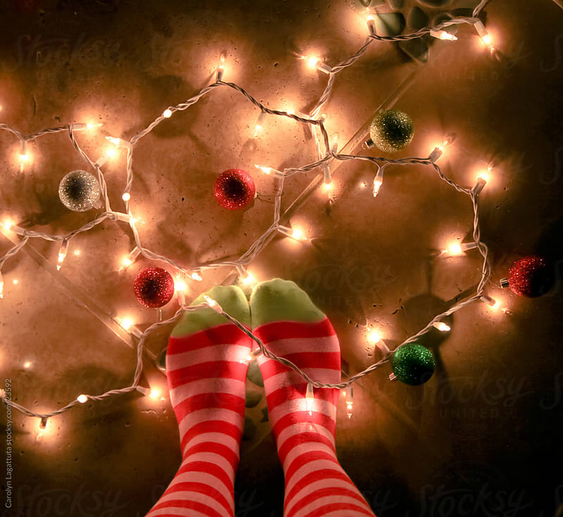 Woman in red and green Christmas socks with Christmas lights on the floor by Carolyn Lagattuta for Stocksy United