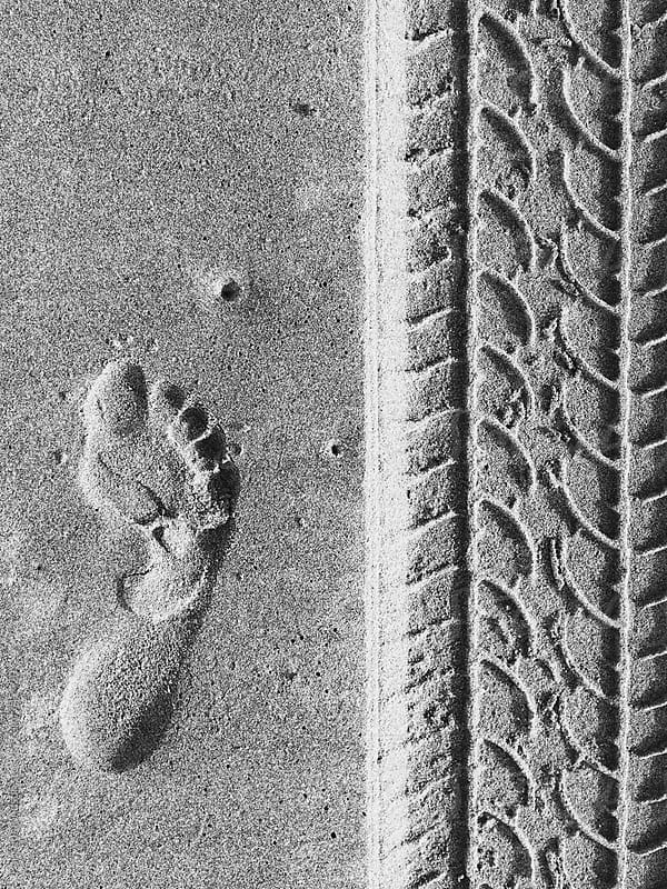 Adult footprint next to tire track in sand by Paul Edmondson for Stocksy United