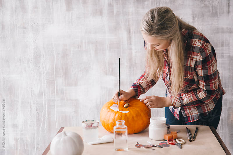 Woman painting on pumpkin using decoupage technique by T-REX & Flower for Stocksy United
