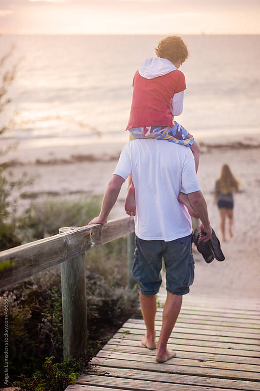 Boy on his father's shoulders walking down boardwalk to beach at sunset by Angela Lumsden for Stocksy United