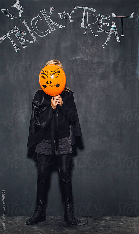 Girl Dressed as a Witch Holding an Orange Balloon by Lumina for Stocksy United