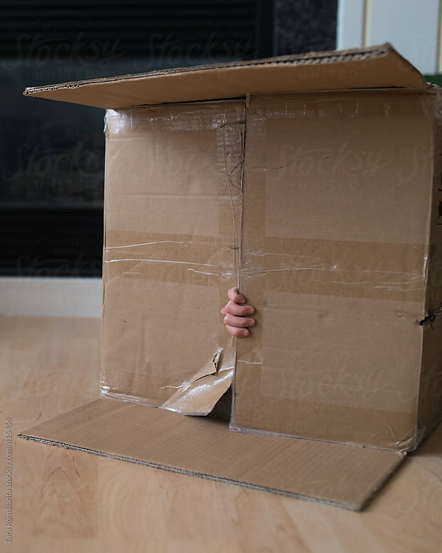 hand on the flap of a cardboard box, child hiding inside by Tara Romasanta for Stocksy United
