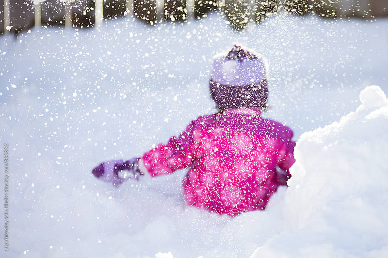 Young girl playing happily in the in the snow by anya brewley schultheiss for Stocksy United