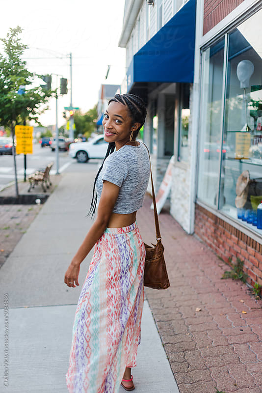 A young african american woman walking in the city by Chelsea Victoria for Stocksy United