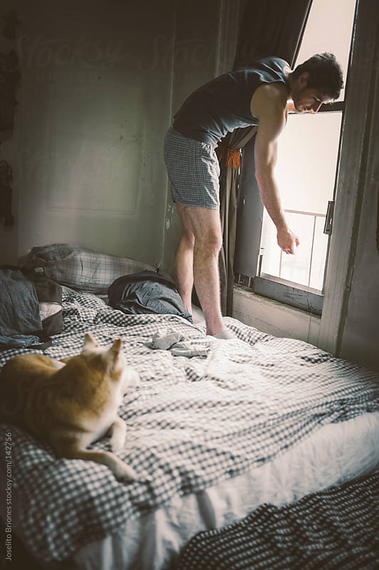 Man Opens Bedroom Window while Pet Dog Watches  by Joselito Briones for Stocksy United