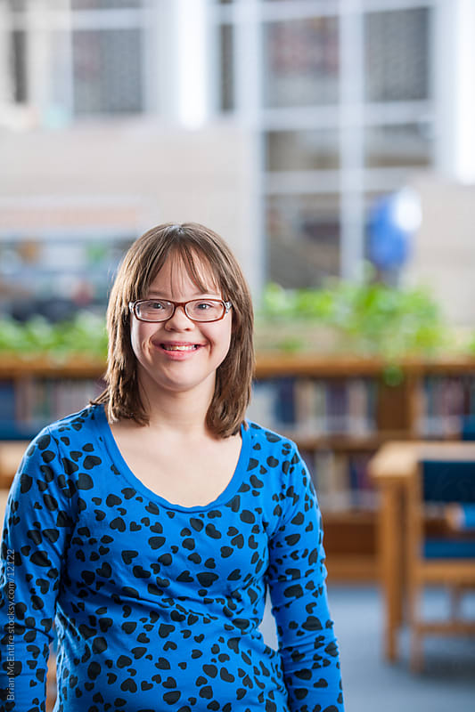 High school student with Down Syndrome Smiling in Library by Brian McEntire for Stocksy United