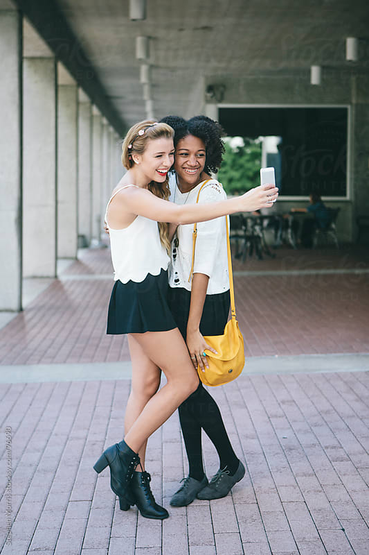 Two Young Women Taking Self Portrait by Stephen Morris for Stocksy United