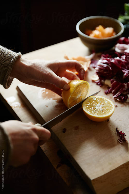 Close up of woman cutting lemon in her kitchen by Trinette Reed for Stocksy United