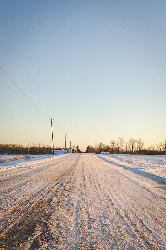 Snowy country road leading to the distant blue sky by Lindsay Crandall for Stocksy United