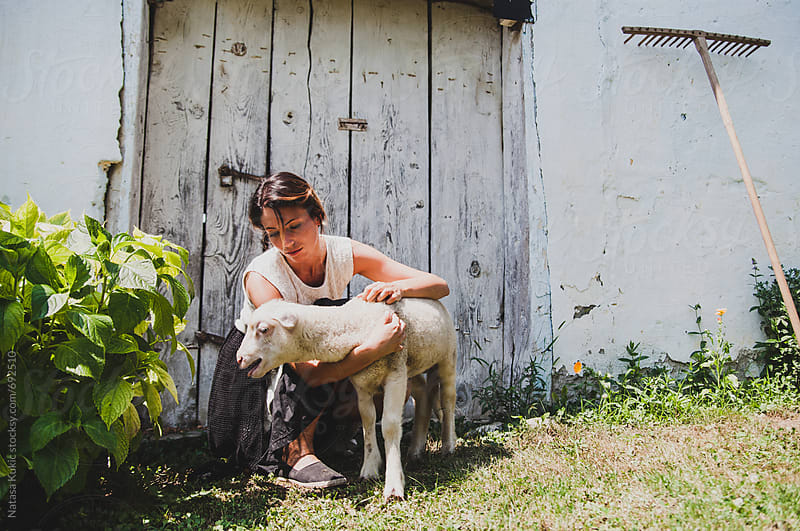 Young woman in the country holding a lamb by Natasa Kukic for Stocksy United