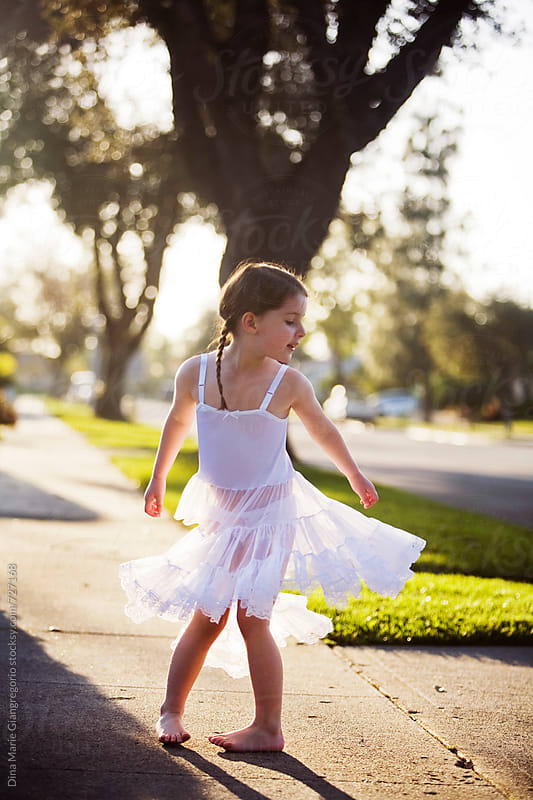 Young Girl Wearing White Slip Dress Twirling On Sidewalk by Dina Giangregorio for Stocksy United