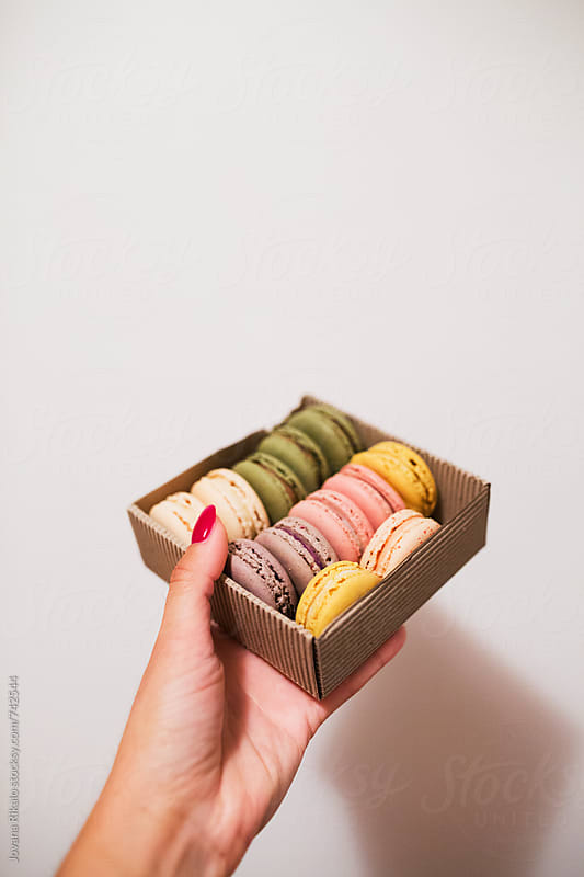 Female hand holding box full of macaroons by Jovana Rikalo for Stocksy United