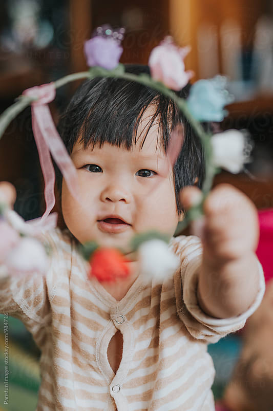 baby girl with wreath by Xunbin Pan for Stocksy United