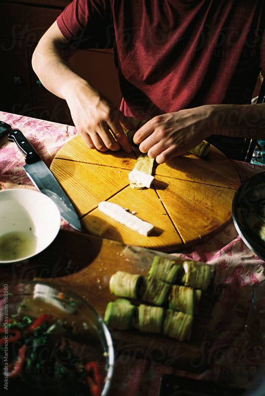 A young man making food by Aleksandra Martinovic for Stocksy United
