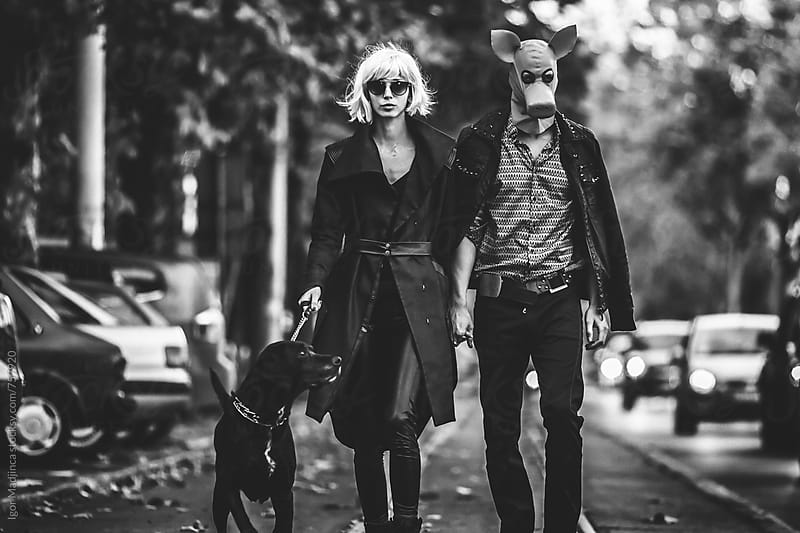 costumed couple walking a black dog on the street, Halloween,black and white by Igor Madjinca for Stocksy United