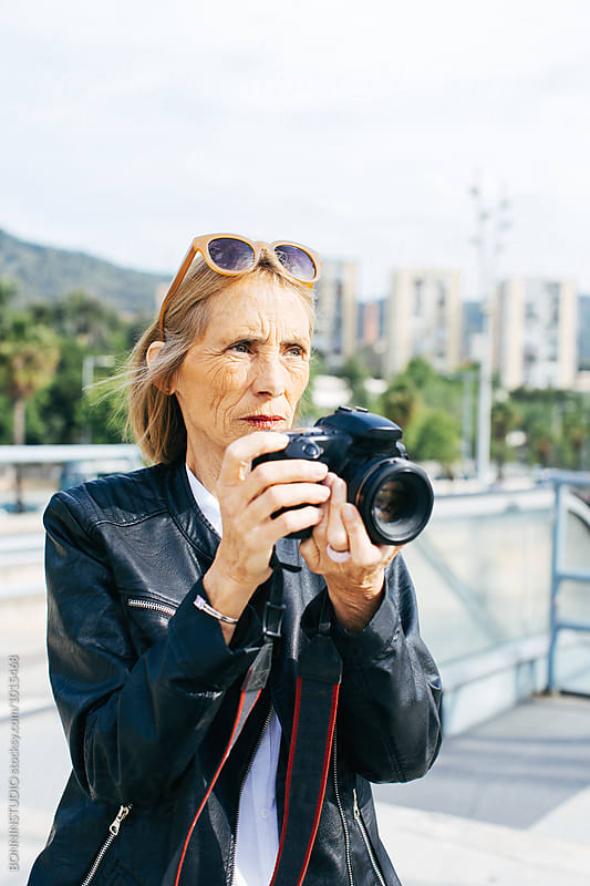 Mature woman taking photos with her camera in the city.  by BONNINSTUDIO for Stocksy United