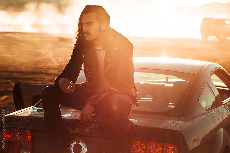 A man sits smoking on the back of his car in the desert sunlight  by HOWL for Stocksy United