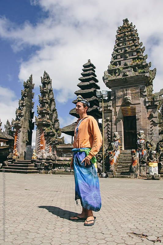Man with asian clothes on temples in Bali, Indonesia by Alejandro Moreno de Carlos for Stocksy United