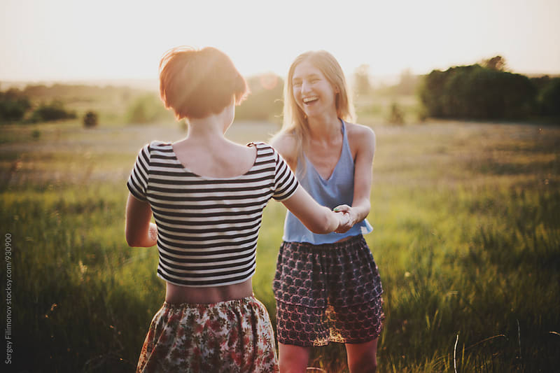 Two female friends dancing on the field by Sergey Filimonov for Stocksy United