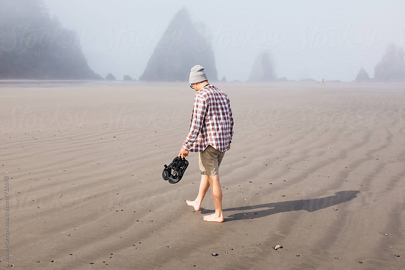 young man walking on beach by Jesse Morrow for Stocksy United