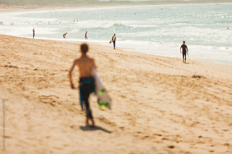 Out of focus scene, surfer walking at the beach by Leandro Crespi for Stocksy United
