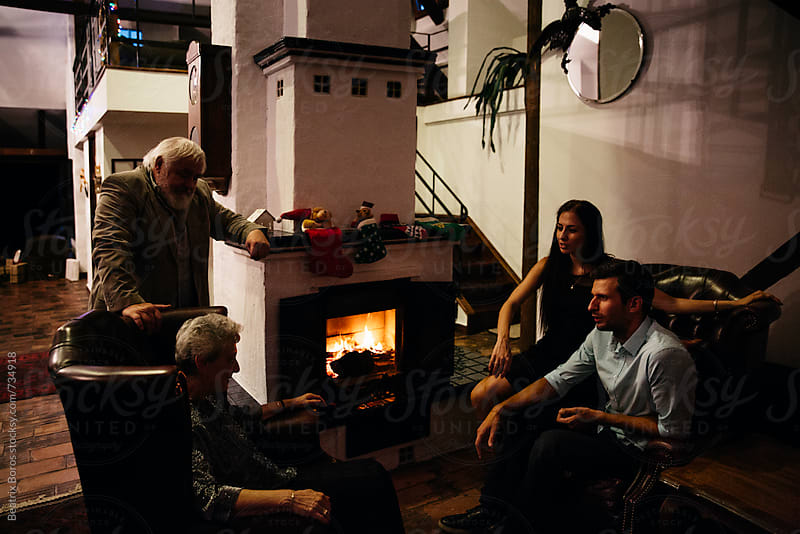 Man woman, and the parents of one of them talking by the fireplace in Winter by Beatrix Boros for Stocksy United