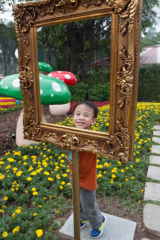 A young kid frames himself for a portrait in a garden setting by Lawrence del Mundo for Stocksy United