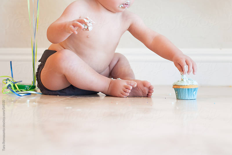 one year old celebrates first birthday with cupcake by Tara Romasanta for Stocksy United