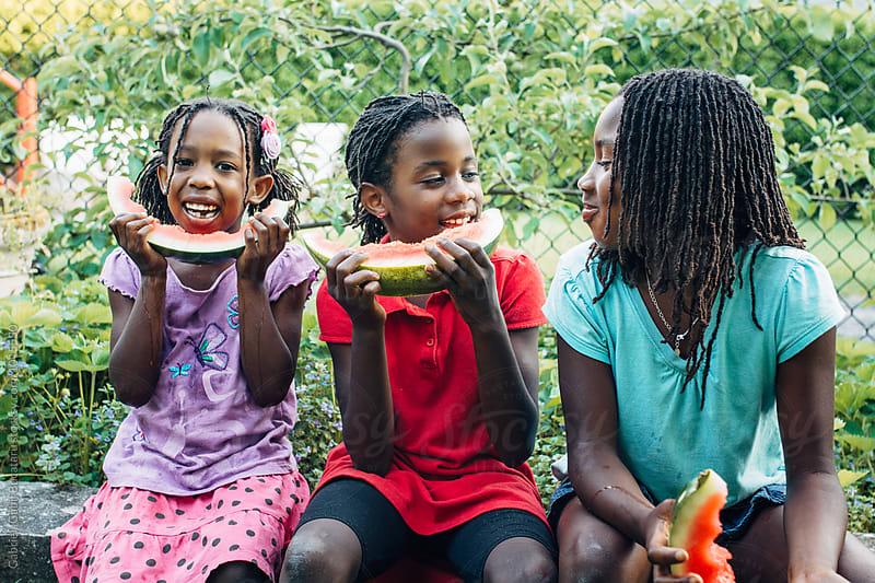 Three black girls eating watermelon by Gabriel (Gabi) Bucataru for Stocksy United