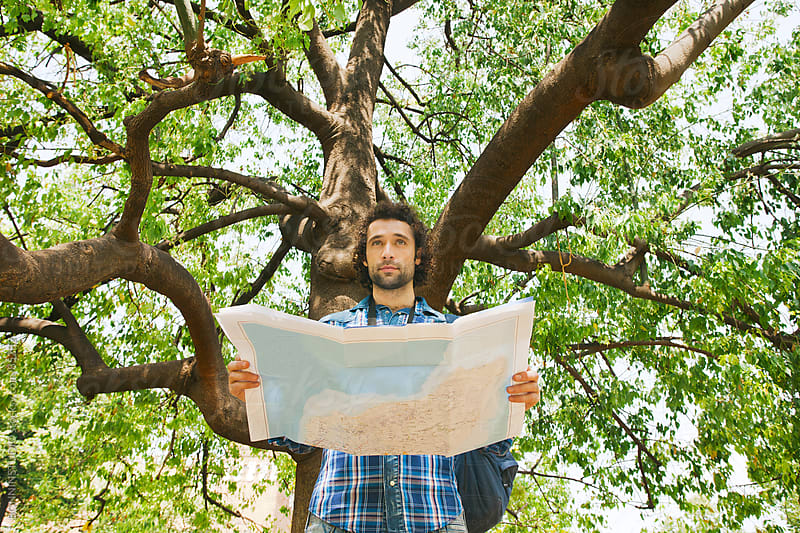 Tourist man visiting a park, he holds a map and instant camera. by BONNINSTUDIO for Stocksy United