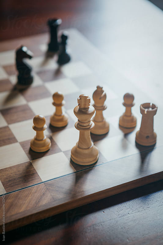 Wooden chess board on a wooden table by Ivan Bastien for Stocksy United