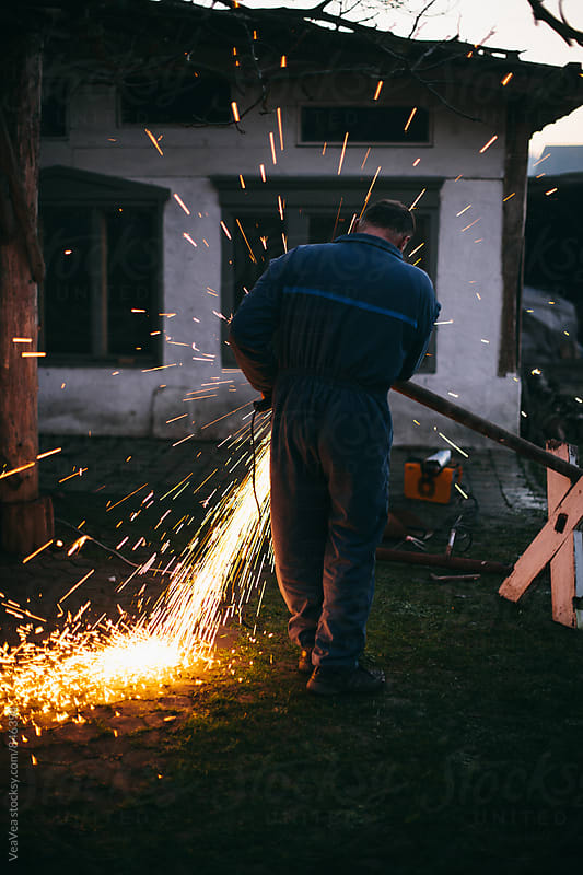 Welder working in the garden during sunset by VeaVea for Stocksy United