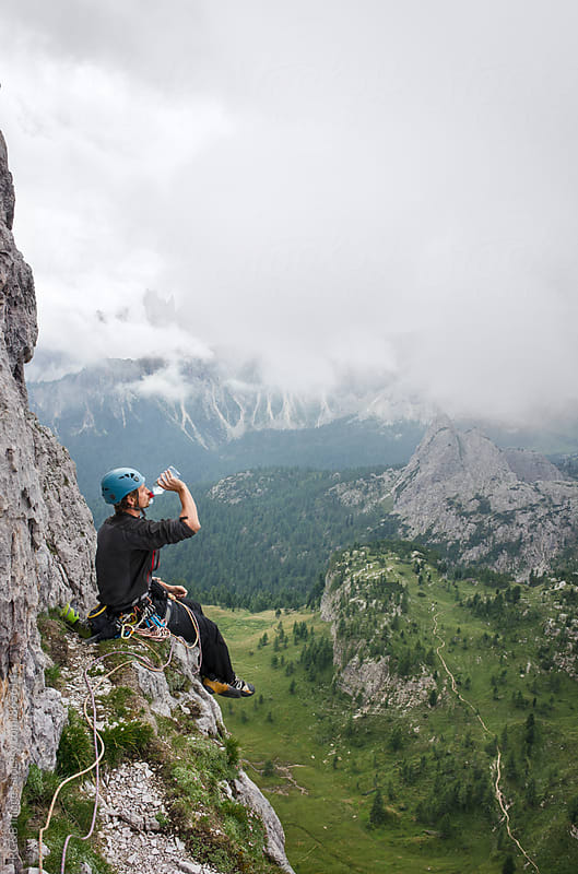 Alpinist resting on a rock ledge high above the ground by RG&B Images for Stocksy United