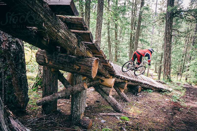 Mountain bike rider on wood bridge from behind on forest by Alejandro Moreno de Carlos for Stocksy United
