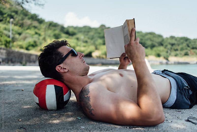 Man reading a book on the sea shore by Boris Jovanovic for Stocksy United