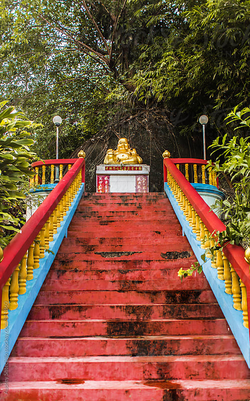 Stairs leading to golden statue of Buddha in the middle of the jungle. by Audrey Shtecinjo for Stocksy United