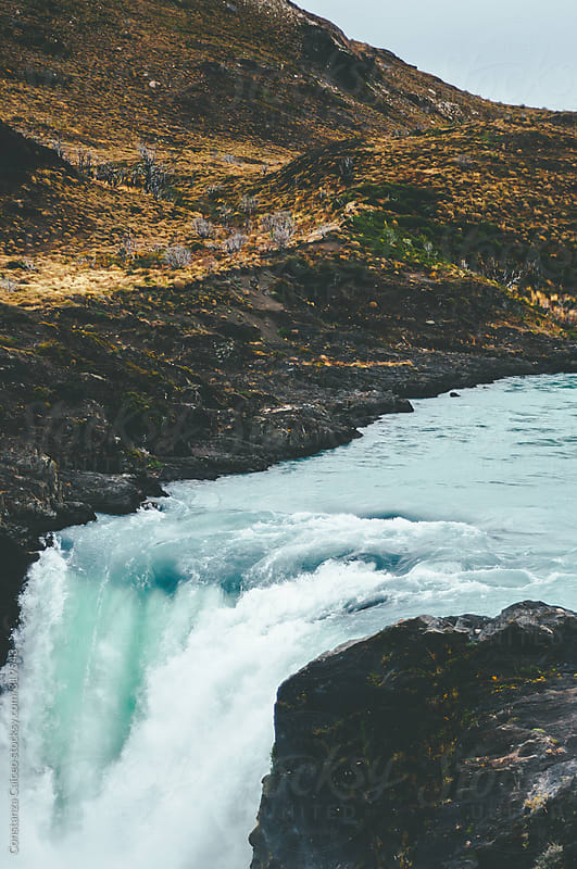 Turquoise waterfall in a cloudy day by Constanza Caiceo for Stocksy United