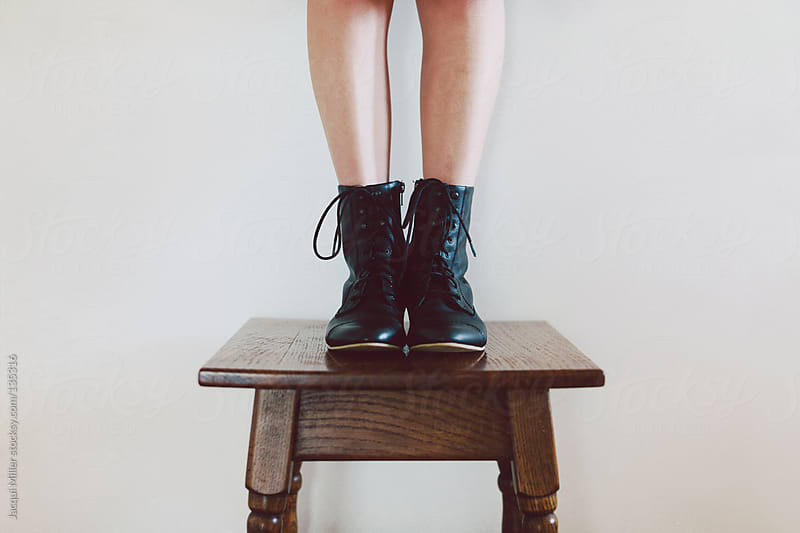 Girl wearing black lace up boots stands on an antique table.  by Jacqui Miller for Stocksy United