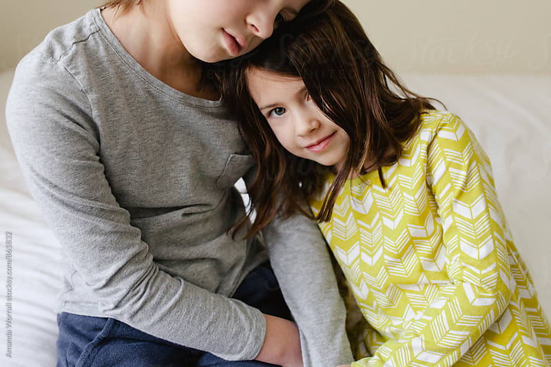 Sisters leaning into each other by Amanda Worrall for Stocksy United