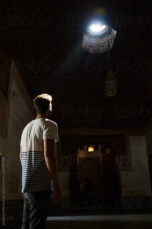 Man looking to a ray of light inside a room of a palace by Alejandro Moreno de Carlos for Stocksy United