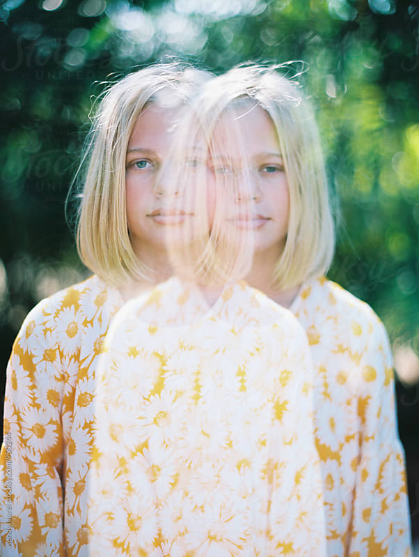 double exposure of teenager with blonde hair and floral dress by wendy laurel for Stocksy United