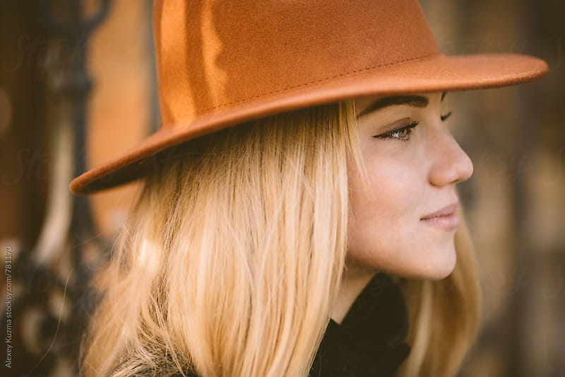 closeup of blond young woman with hat by Alexey Kuzma for Stocksy United