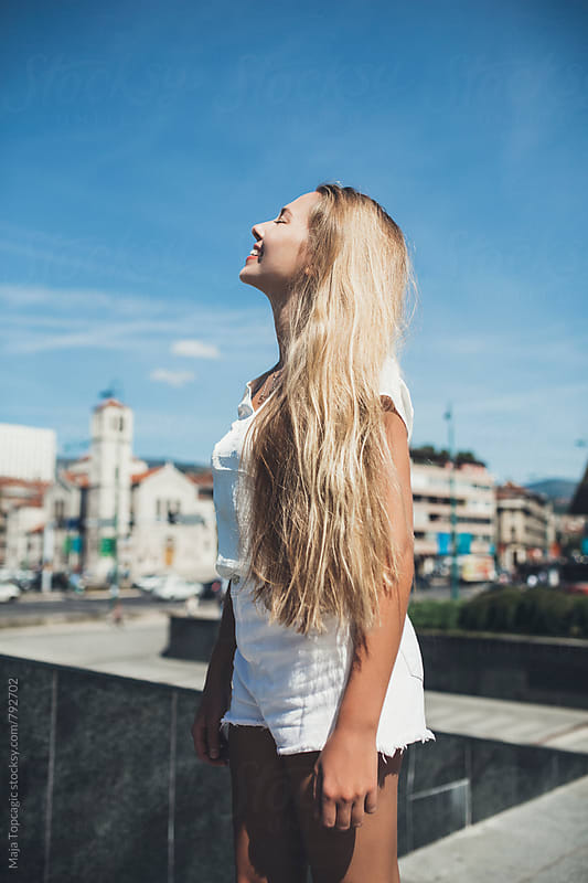 Young beautiful blond woman smiling in the city by Maja Topcagic for Stocksy United