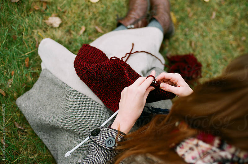 Young woman knitting outdoors by Lyuba Burakova for Stocksy United